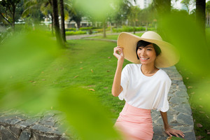 Image of a smiling young woman in the sombrero hat sitting in the park and resting on the foreground