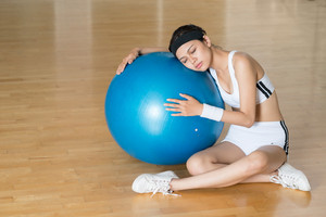 Image of a tired gymnast leaning against a fitness-ball