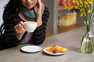 Image of a woman drinking hot coffee, a tasty snack is on the foreground