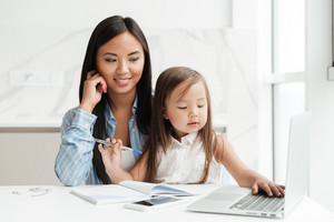 Image of amazing young mom sitting at the table with little cute asian girl at home indoors using laptop computer writing notes to notebook. Looking aside.