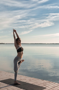 Image of amazing young sports lady standing at the beach make yoga exercises.