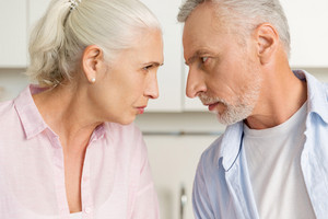 Image of angry mature man standing near mature serious woman at the kitchen. Looking at each other.