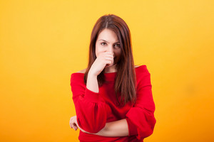Image of beautiful young woman looking at the camera over yellow background. Gorgeous young woman. Stylish woman.