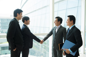 Image of business partners handshaking inside on the foreground