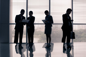 Image of business silhouettes standing at the office