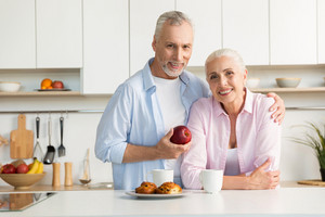 Image of cheerful mature loving couple family standing at the kitchen. Man holding apple. Looking at camera and hugging.