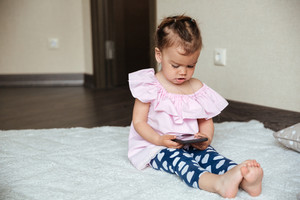 Image of concentrated little girl child sitting on bed indoors using mobile phone. Looking aside.