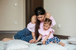 Image of concentrated young mother with her little daughter lies on bed indoors and chatting by phone. Looking aside.