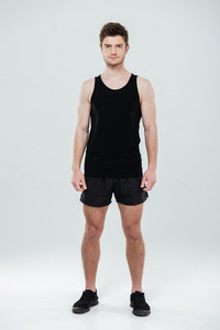 Image of concentrated young sportsman standing isolated over white background. Looking at camera.