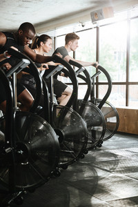 Image of group of multiethnic sports strong people make sport exercise with spinning bicycles.