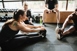Image of group of sports strong people sitting in gym make stretching exercises. Looking aside.