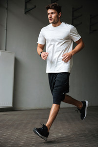 Image of handsome young sports man running at the stadium outdoors looking aside.