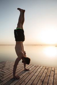 Image of handsome young sportsman make yoga exercises at the beach.