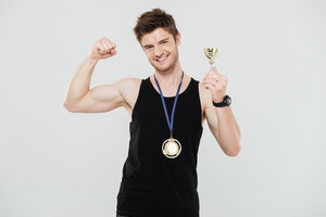 Image of handsome young sportsman with medal and reward standing isolated over white background showing biceps.