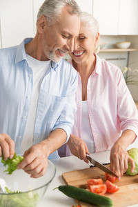 Image of happy mature loving couple family standing at the kitchen and cooking salad. Looking aside.