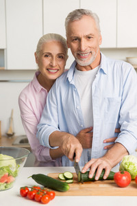 Image of happy mature loving couple family standing at the kitchen using laptop computer and cooking salad. Looking at camera.