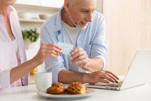 Image of happy mature loving couple family standing at the kitchen using laptop computer holding credit card. Looking aside.