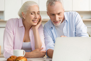 Image of happy mature loving couple family standing at the kitchen using laptop computer. Looking aside.