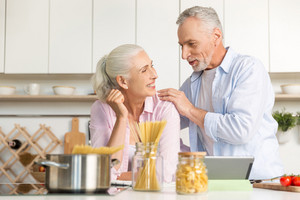 Image of happy mature man standing near mature cheerful woman at the kitchen cooking at using tablet computer. Looking at each other.
