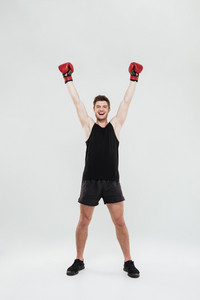 Image of happy screaming young sportsman boxer standing isolated over white background. Looking at camera.
