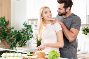 Image of happy young loving couple standing at kitchen and cooking together. Looking aside.