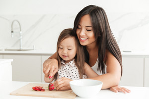 Image of happy young mom with little cute asian daughter at home indoors at the kitchen cut the strawberry. Looking aside.