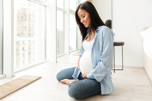 Image of happy young pregnant woman sitting at home indoors looking aside.