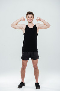 Image of happy young sportsman standing isolated over white background. Looking at camera showing biceps.