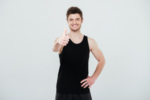 Image of happy young sportsman standing isolated over white background. Looking at camera showing thumbs up gesture.