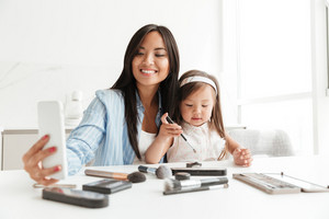 Image of happy young woman with little daughter at home indoors make selfie near table with cosmetics.