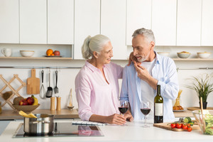 Image of mature happy loving couple family standing at the kitchen drinking wine. Looking aside.