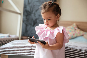 Image of serious little girl child indoors using mobile phone. Looking aside.