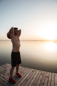 Image of serious young sportsman make sport exercises with ball at the beach. Looking aside.