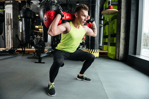 Image of young concentrated sportsman make sport exercises in gym. Looking aside.