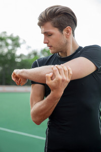 Image of young male athlete make stretching exercises outdoors. Looking aside.