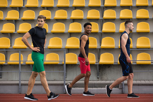 Image of young smiling multiethnic athlete group on running track outdoors. Looking aside.
