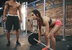 Instructor assisting woman during lifting barbell