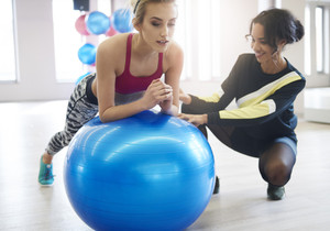Instructor helping woman balancing on fitness ball