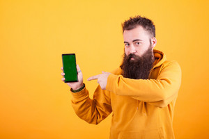 Intrigued bearded hipster man pointing at smartphone over yellow background. Yellow hoodie. Handsome man. Modern technology