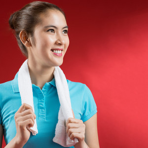 Isolated image of a sweating sportswoman over a red background