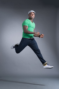 Isolated portrait of a cool sportsman jumping over a grey background