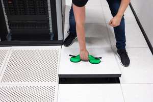 IT Engineer Pulling Floor Tile Using Suction Cups In Datacenter