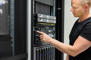 IT Technician Monitors Server On Rack In Datacenter