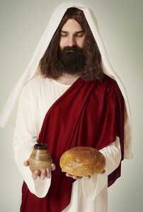 Jesus with eyes closed holding wine and bread