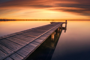 Jetty at sunset on a peaceful lake