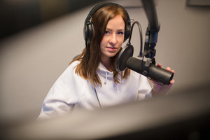 Jockey Using Headphones And Microphone In Studio