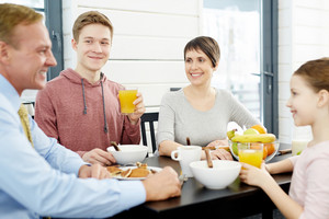 Joyful family members gathered together in dining room, enjoying tasty breakfast and chatting animatedly, waist-up portrait