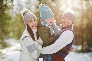 Joyful family of three looking at camera in winter park