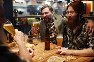 Joyful men having nice time in pub