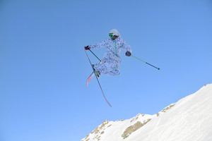 jumping freestyle skier at mountain with fresh snow fresh sunny winter day